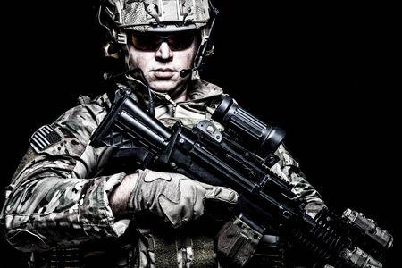Soldado del ejército estadounidense con rifle sobre fondo negro Foto de archivo