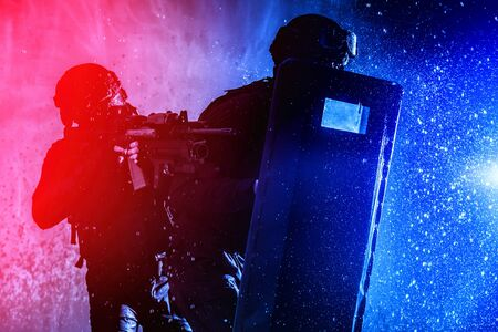 SWAT fighters officers hiding behind ballistic shield