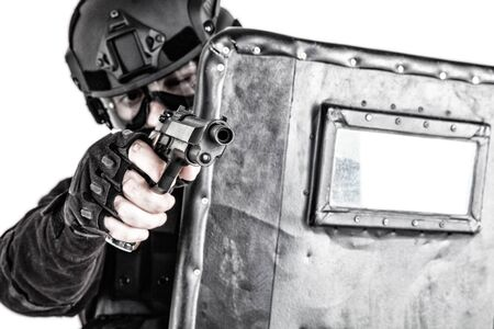 SWAT team fighter aiming pistol from behind shield Banque d'images