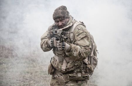 Soldier in camouflage uniform, wearing military ammunition, aiming service rifles, covering each other, shooting in competitors, attacking enemies trough smoke screen Stock Photo