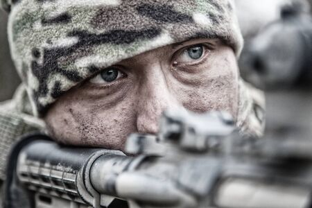 Close-up portrait of army infantryman, modern warfare combatant, young soldier with dirty, unshaven face, in camo bennie hat, aiming service rifle, controlling area with gunfire, looking in camera Stock Photo - 135846395