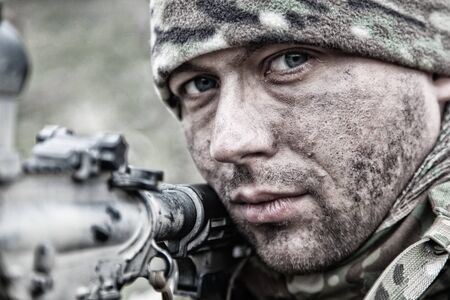 Close-up portrait of army infantryman, modern warfare combatant, young soldier with dirty, unshaven face, in camo bennie hat, aiming service rifle, controlling area with gunfire, looking in camera Archivio Fotografico