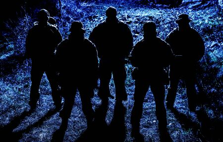 Group of armed soldiers, modern military mercenaries, secret service fighters, army special operations riflemen, commandos crew standing together in line in darkness, patrolling area at nighttime Stock Photo