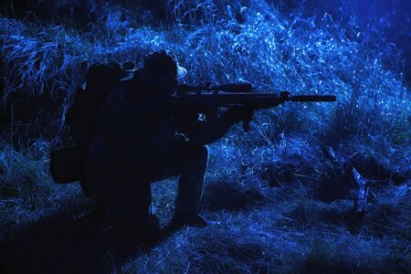 Army elite soldier, special forces fighter, infantry rifleman aiming service rifle with silencer in darkness, searching targets to shoot on stealth mission, spying and observing enemies positions Stock Photo
