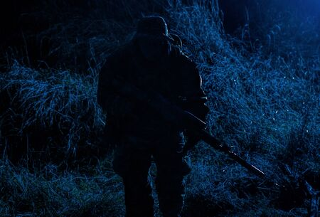 Soldat d'élite de l'armée, combattant des forces spéciales, fusilier d'infanterie visant un fusil de service avec silencieux dans l'obscurité, recherchant des cibles pour tirer en mission furtive, espionnant et observant les positions des ennemis Banque d'images