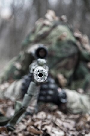 Close up image of sniper rifle silencer muzzle, front view. Army elite forces shooter lying on ground in forest. Commando sniper hiding, masked himself in dry leaves. Marksman shooting from ambush