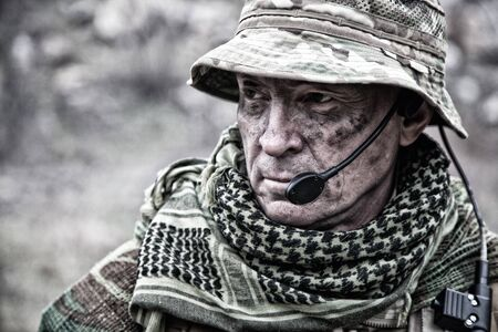 Close-up portrait of brutal commando veteran, experienced army commander or officer with dirty face, wearing camouflage bonnie, shemagh, tactical radio headset with microphone, looking in camera