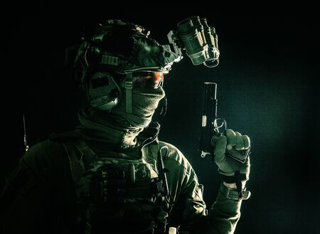 Combatant armed with service pistol in darkness Фото со стока