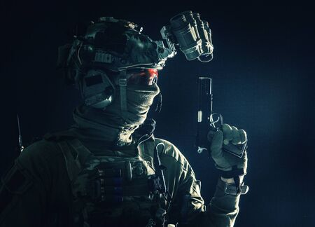 Combatant armed with service pistol in darkness Standard-Bild