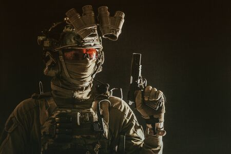 Combatant armed with service pistol in darkness Banque d'images