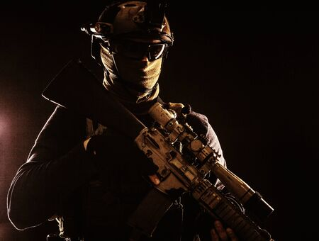Army elite troops marksman, special operations forces sniper wearing mask and glasses, night-vision or infrared thermal imaging device on helmet, holding service rifle with optical sight and silencer