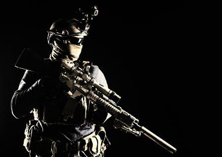 Scharfschütze der Armee-Elitetruppen, Scharfschütze der Sondereinsatzkräfte mit Maske und Brille, Nachtsicht- oder Infrarot-Wärmebildgerät am Helm, Dienstgewehr mit optischem Visier und Schalldämpfer haltend
