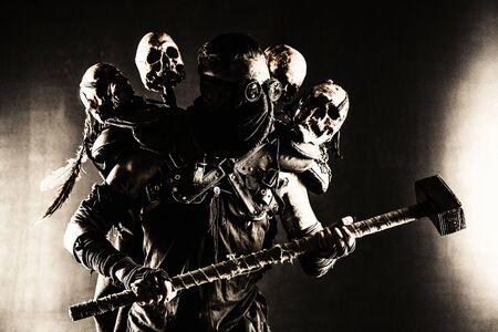 Survivant post-apocalyptique, harceleur de zone radioactive, tueur en série fou ou maniaque en masque à gaz et vêtements en lambeaux décorés de runes, menaçant avec un marteau isolé sur un tournage en studio noir Banque d'images