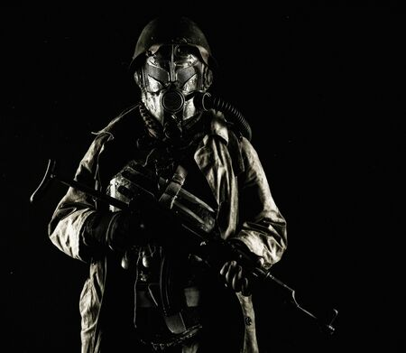 Nuclear post-apocalypse survivor, alternative history nazi soldier or partisan in wool field cap, face gas mask, glasses and handmade armor, with rifle gun studio shoot