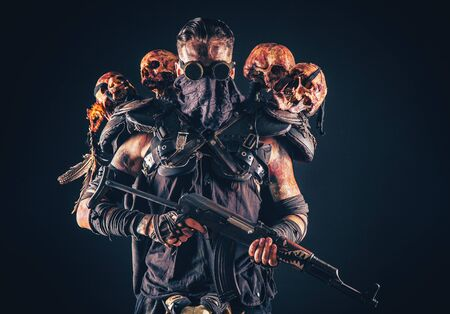 Post apocalyptic survivor, radioactive zone stalker, crazy serial killer or maniac in glasses and skulls on shoulders, with automatic rifle