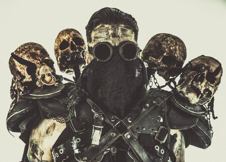 Survived in nuclear disaster mutant bandit or underground human creature, wearing rags and human skulls on shoulders 스톡 콘텐츠