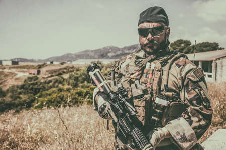Navy SEALs fighter in ballistic goggles, equipped military ammunition and body armour, holding service rifle, looking in camera while standing outdoors. Special forces soldier half-length portrait Standard-Bild
