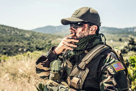 Army special forces soldier, SEALs fighter in camo uniform, shemagh scarf, ballistic glasses and cap, wearing tactical plate carrier, smoking cigarette, resting after fight in mountain area