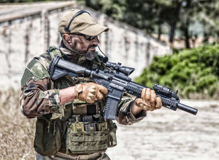 Private military company mercenary, brutal looking special forces fighter in battle uniform and plate carrier, wearing radio headset and sunglasses, holding service rifle in hands, ready to fight Standard-Bild