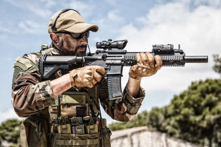 Private military company mercenary, brutal looking special forces fighter in battle uniform and plate carrier, wearing radio headset and sunglasses, holding service rifle in hands, ready to fight Foto de archivo
