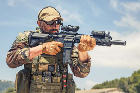 Private military company mercenary, brutal looking special forces fighter in battle uniform and plate carrier, wearing radio headset and sunglasses, holding service rifle in hands, ready to fight Banque d'images