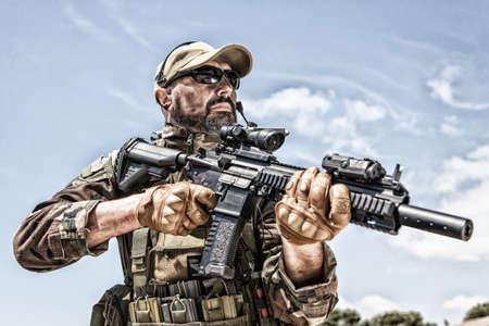 Private military company mercenary, brutal looking special forces fighter in battle uniform and plate carrier, wearing radio headset and sunglasses, holding service rifle in hands, ready to fight