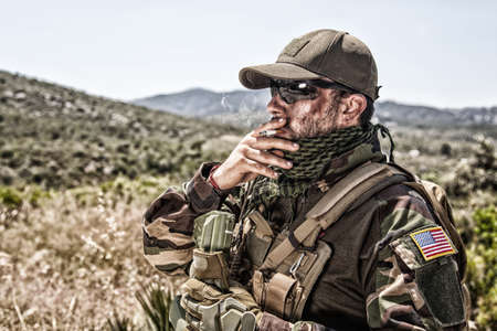Army soldier, commando shooter in ammunition and battle uniform, standing in mountain area, looking into distance and smoking cigarette. Special operations forces fighter during mission Standard-Bild
