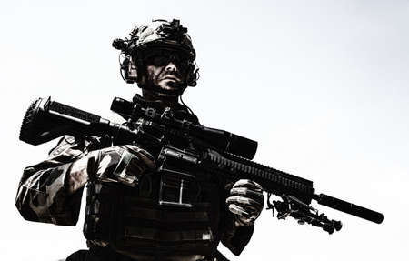 Half-length portrait of special forces sniper or marksman, army soldier in camouflage uniform and helmet with radio headset, standing on background of blue sky, holding sniper rifle with optical scope