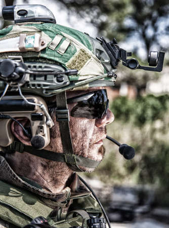 Shoulder portrait of army soldier, special forces fighter, modern warfare combatant with dirty, unshaven face, wearing sunglasses, combat helmet and talking in tactical radio headset during mission