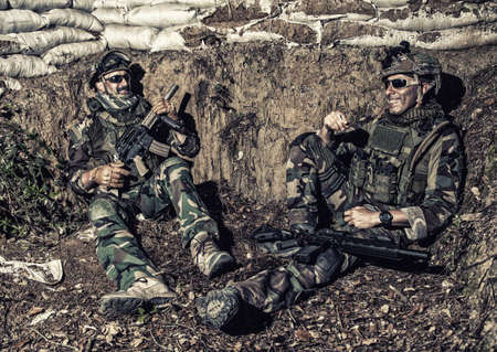 Navy SEALs soldiers, special operations forces fighters in camouflage uniform, body armor and helmet, armed assault rifles, sitting in trench, resting after fight, talking and joking with comrades Stock Photo