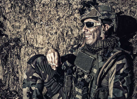 Smiling US army soldier, SEALs fighter, modern combatant in combat uniform, plate carrier, ballistic glasses and battle helmet resting after fight, sitting in trench at night and smoking cigarette