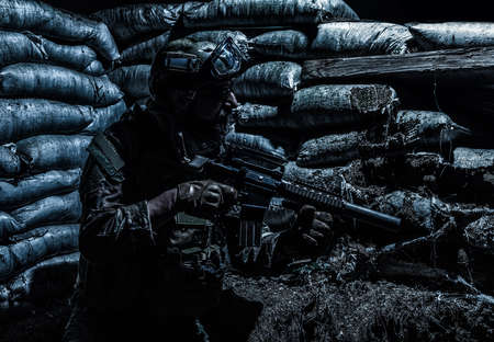 Navy SEALs fighter, army soldier in combat uniform, goggles and battle helmet at night watch, sitting with assault rifle in trench with sandbags, looking in loophole, waiting for enemy attack