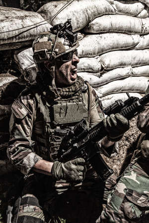 Navy SEALs rifleman, army soldier in combat uniform and helmet, grabbing assault rifle, screaming, yelling while covering behind sandbags. Special forces infantryman attacking enemies in trench Standard-Bild