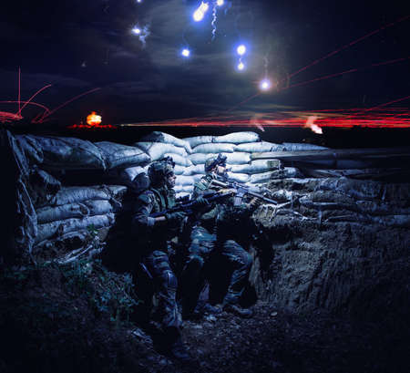 Army soldiers armed assault rifles, hiding in trench during night action. Navy SEALS team fighters, commando shooters with weapon, watching on falling flares in sky, waiting for signal to attack