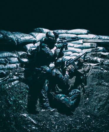 Soldiers covering from enemy fire in trench. Two Navy SEALs fighters, infantrymen in camouflage uniform and helmet, armed service rifles, hiding behind sandbags during night attack or gunfight