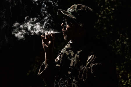 Commando soldier in camouflage uniform, ballistic glasses and bonnie, inhale cigarette smoke, smoking tobacco or marijuana joint in forest or jungles at night. Army infantryman relaxing after fight Standard-Bild
