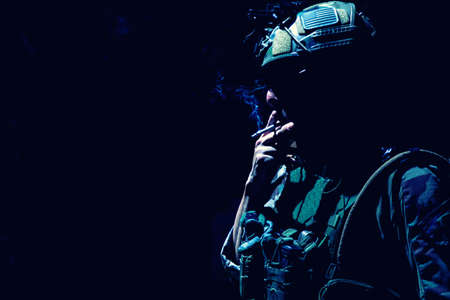 Army soldier in combat uniform and helmet, smoking cigarette in darkness. Special operations forces fighter, resting infantryman silhouette with cigarette in mouth and tobacco smoke, low key Standard-Bild