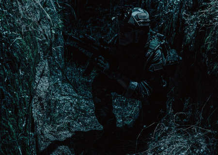 Army soldier, special forces infantryman in combat uniform and helmet, armed assault rifle, sneaking in darkness, crawling in trench at night. Commando fighter, combatant hiding from enemy fire Standard-Bild