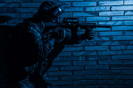 Army soldier, counter terrorist squad fighter in camouflage uniform, load carrier and goggles on helmet, sneaking in darkness along brick wall, aiming service rifle with silencer during indoor fight