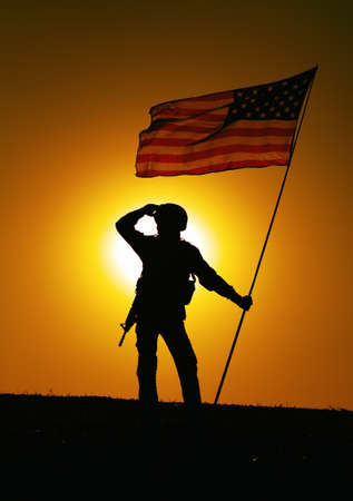 Silhouette of US army soldier, Marines Corps fighter or special forces rifleman in helmet, armed rifle standing on hill with waving on wind national flag, looking far away on background of sunset sky