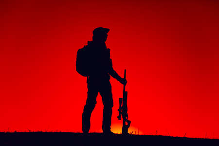 Silhouette of army special forces sniper standing with rifle on background of sunset sky. Commando fighter in boonie hat and ammunition patrolling area at nighttime. Hunter hunting on sunset or dawn