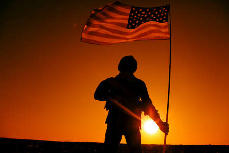 Silhouette of US army soldier, special operations shooter holding waving on flagpole national flag while standing on background of sunset. American army hero, United States or America military victory 写真素材