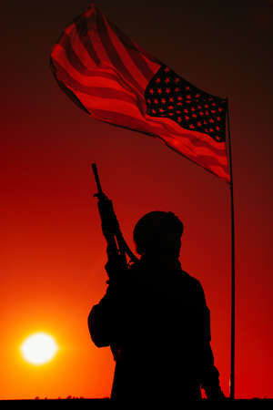 Silhouette of US army infantry soldier, special forces rifleman in combat helmet, armed assault rifle standing under waving United States of America national flag with setting sun on background 写真素材