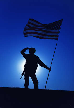 Silhouette of American army soldier, Marines rifleman saluting and holding waving on wind national flag on background of night sky with moon backlight. Heroism and patriotism, military honor concept 写真素材
