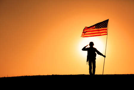 Silhouette of USA armed forces soldier, army infantryman or Marine Corps fighter veteran saluting while standing with national flag on sunset background. Military victory and glory, fallen remembrance 写真素材