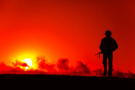 Silhouette of army soldier with service rifle walking to horizon with sunset and smoke. Special operations forces fighter, military company mercenary waking on battlefield after fight, patrolling area