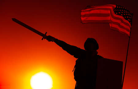 Silhouette of USA army soldier standing under national flag, holding shield, raising and pointing sword forward on sunset background. Soldier duty and honor, national hero and military victory concept 写真素材