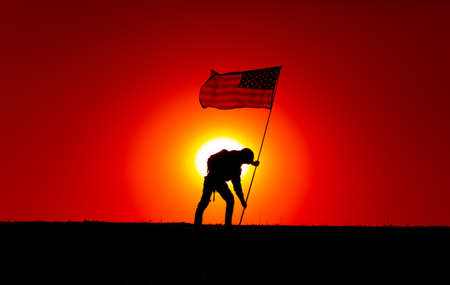 Silhouette of army soldier, United States of America infantryman sticking into ground flagpole with waving USA national flag. Soldiers heroism and victory, military honor and memory of fallen warriors 写真素材