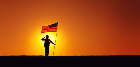 Silhouette of USA armed forces soldier, army infantryman or Marine Corps fighter saluting while standing with waving national flag on sunset background. Military victory and glory, fallen remembrance 写真素材