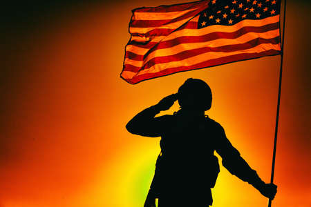 Silhouette of army soldier in combat helmet, armed service rifle, holding USA national flag, saluting on background of sunset or dawn sky. Military respect and honor, patriotism and heroes remembrance